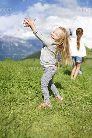 Group Of Children Making Giant Bubbles In Countrysideの写真素材 [FYI02123894]