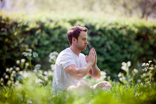 A young man meditating outdoorsの写真素材 [FYI02123898]