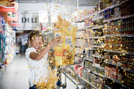 Naughty young girl emptying cereal packet in a supermarketの写真素材 [FYI02123900]