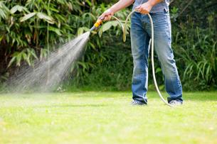 Man using hose watering green lawn yardの写真素材 [FYI02123913]