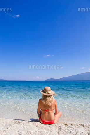 Woman, looking out to sea, sitting on sunny beachの写真素材 [FYI02123920]