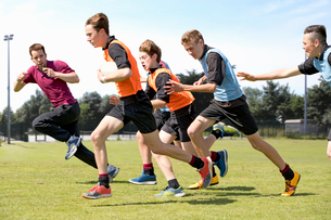 Middle schoolboys and teacher running playing rugby on field in physical education classの写真素材 [FYI02123925]