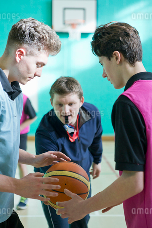 Gym teacher initiating basketball tip-off for high school studentsの写真素材 [FYI02123926]