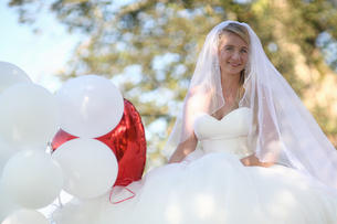 Portrait Of Bride Outdoors With Balloons On Wedding Dayの写真素材 [FYI02123944]