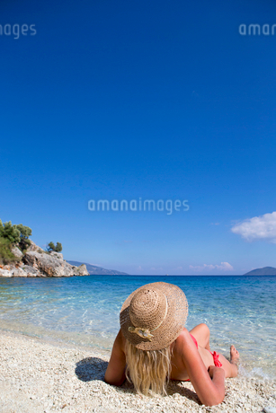 woman, looking out to sea, lying on beachの写真素材 [FYI02123949]