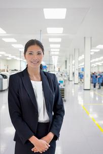 Portrait Of Businesswoman On Floor Of Engineering Factoryの写真素材 [FYI02123956]
