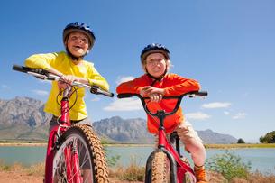 Portrait of children on mountain bikes by lakeの写真素材 [FYI02123966]