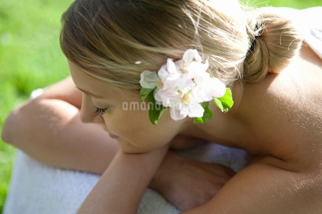 A young woman laying on a massage table with blossom in her hairの写真素材 [FYI02123967]
