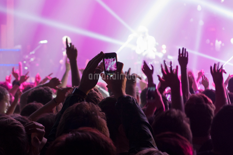 Music Fan Taking Picture On Mobile Phone At Rock Concertの写真素材 [FYI02123973]