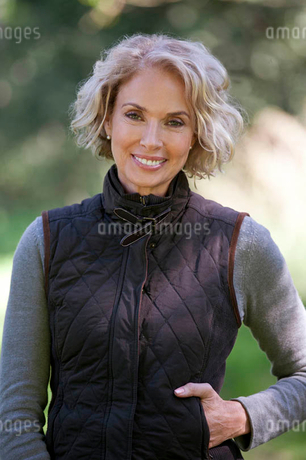 A portrait of a mature woman standing outdoors, smilingの写真素材 [FYI02123975]