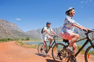Senior couple mountain biking on mountain trackの写真素材 [FYI02123984]