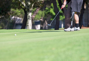 Close Up Of Male Golfer With Artificial Leg Putting Ball On Greenの写真素材 [FYI02124020]