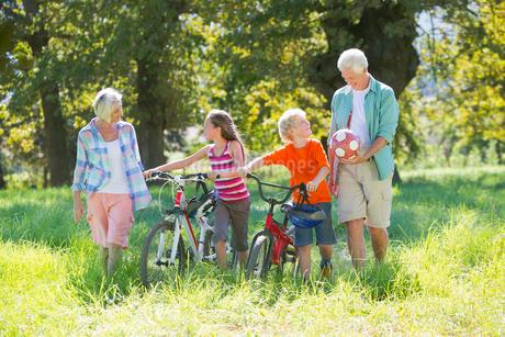 Multi generation family, pushing mountain bikes, in treelined fieldの写真素材 [FYI02124022]