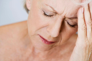 A senior woman with a headache, touching her foreheadの写真素材 [FYI02124025]