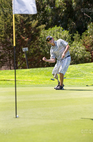 Male Golfer With Artificial Leg On Course Putting Ball Into Holeの写真素材 [FYI02124047]