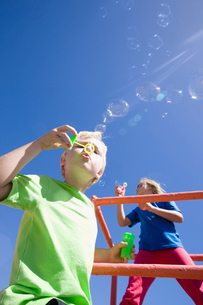 Children blowing bubbles on monkey bars at playgroundの写真素材 [FYI02124051]