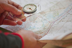 A man holding a map and compass, close upの写真素材 [FYI02124053]
