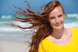 Portrait of smiling woman with red hair on sunny beachの写真素材 [FYI02124071]