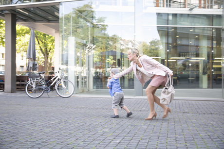 Businesswoman Pulling Reluctant Son Along Outside Officeの写真素材 [FYI02124082]