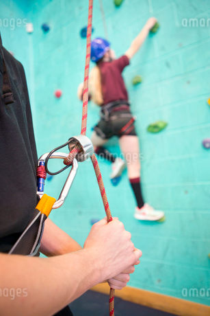 High school student holding rope supporting classmate climbing rock climbing wallの写真素材 [FYI02124083]