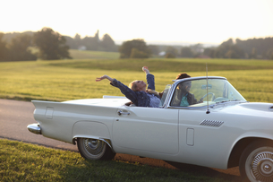 Couple Driving On Country Road In Open Top Classic Carの写真素材 [FYI02124090]