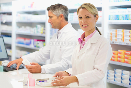 Pharmacist counting pills at pharmacy counterの写真素材 [FYI02124095]