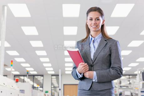 Portrait Of Businesswoman On Floor Of Engineering Factoryの写真素材 [FYI02124107]