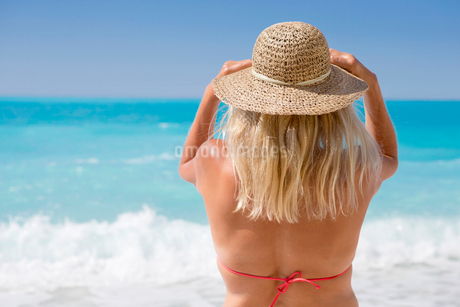 woman, looking out to sea, standing on sunny beachの写真素材 [FYI02124115]