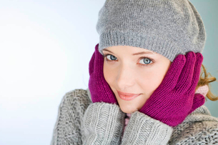 A young woman with her hands over her ears, trying to keep warmの写真素材 [FYI02124123]