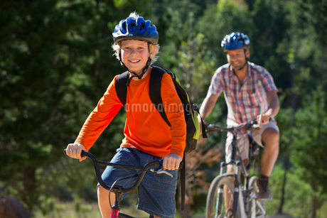 Father and son riding mountain bikes in forestの写真素材 [FYI02124132]