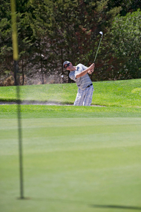 Male Golfer Hitting Ball Out Of Bunker Onto Greenの写真素材 [FYI02124140]