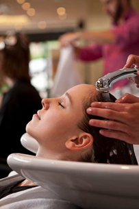 A female client having her hair washed in a hairdressing salon, close upの写真素材 [FYI02124143]
