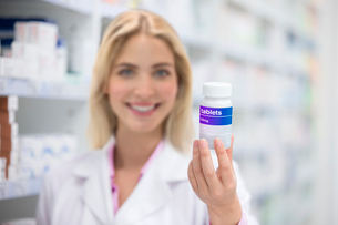 Female Chemist In Pharmacy Holding Container Of Tabletsの写真素材 [FYI02124146]