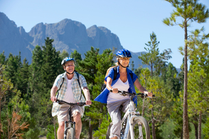 Older couple riding mountain bikes in forestの写真素材 [FYI02124156]