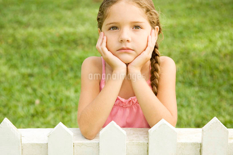 little girl leaning on fence looking sadの写真素材 [FYI02124163]