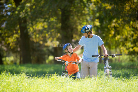 Father and son pushing mountain bikes, in treelined fieldの写真素材 [FYI02124174]
