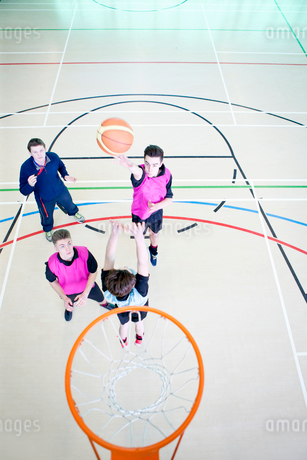 High school students playing basketball in gym classの写真素材 [FYI02124180]