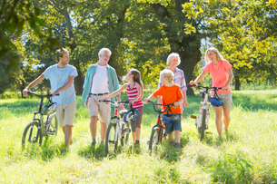 Multi generation family, pushing mountain bikes, in treelined fieldの写真素材 [FYI02124182]