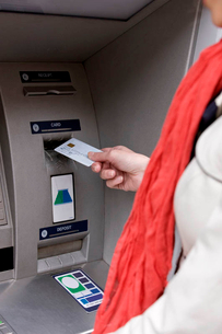 A woman using a cash machine, close-upの写真素材 [FYI02124185]