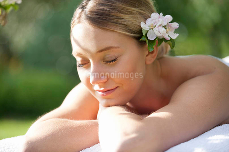 A young woman laying on a massage table with eyes closed, close upの写真素材 [FYI02124217]