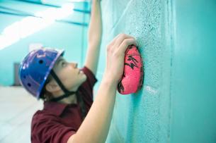 Focused high school student climbing rock climbing wallの写真素材 [FYI02124226]