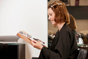 A female client reading a magazine whilst she has her hair coloured in a hairdressing salon, close uの写真素材 [FYI02124231]