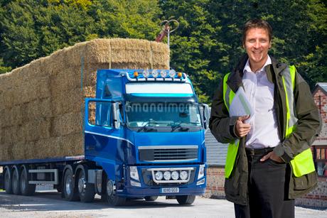 Man Standing By Weighbridge As Lorry Transports Straw Balesの写真素材 [FYI02124240]