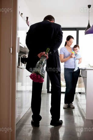 A man returning home to his family after work, holding a bunch of rosesの写真素材 [FYI02124253]