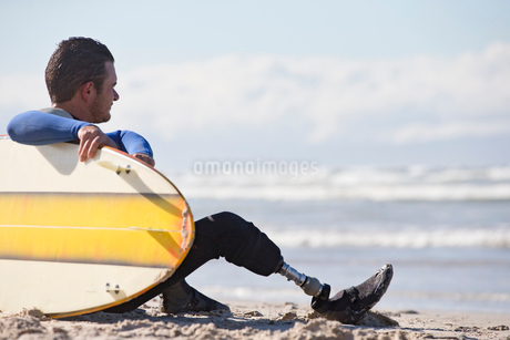 Surfer With Artificial Leg Sitting On Beachの写真素材 [FYI02124258]