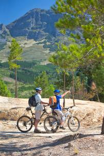 Senior couple mountain biking on mountain pathの写真素材 [FYI02124272]