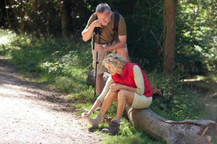 A mature couple resting beside a country path, woman massaging her sore feetの写真素材 [FYI02124295]