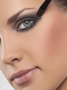 Close-up portrait of young woman applying eyeshadow, studio shotの写真素材 [FYI02124299]