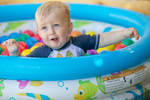 Baby Boy Playing In Outdoor Paddling Pool Filled With Ballsの写真素材 [FYI02124305]