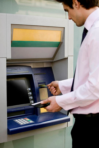 A businessman using a cash machineの写真素材 [FYI02124317]
